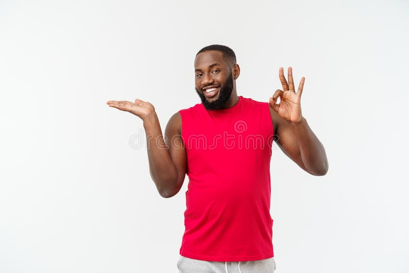 Mãos de alargamento do homem afro-americano novo do esporte ao lado para que convidar venha imagem de stock