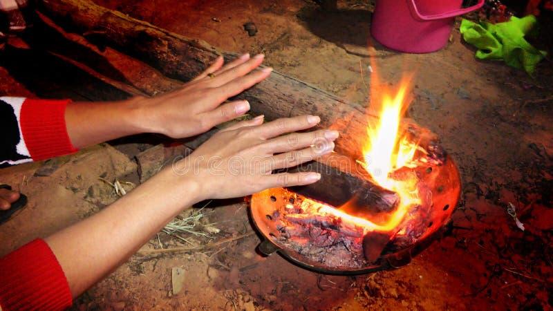 Mãos de aquecimento pelo incêndio foto de stock