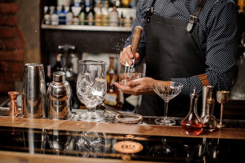Mãos de Barmans que esmagam um cubo de gelo grande fotografia de stock royalty free
