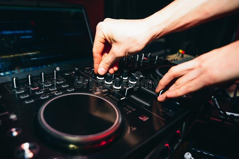 Mãos de controladores do DJ para a música no misturador profissional para a música de mistura imagens de stock royalty free