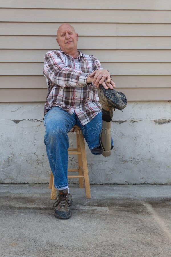 Mãos de descanso assentadas do homem do amputado na sapata do pé protético imagem de stock