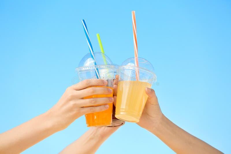 Mãos de jovens mulheres bonitas com bebidas imagens de stock royalty free