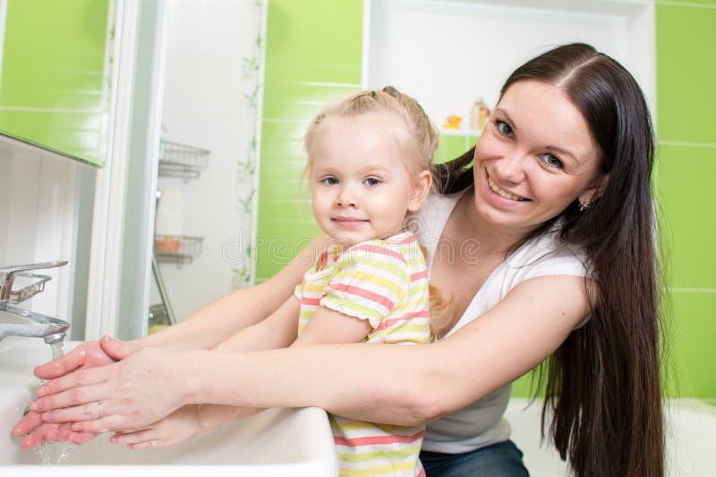 Mãos de lavagem bonitas da menina da criança da mulher e da filha com sabão no banheiro imagens de stock royalty free