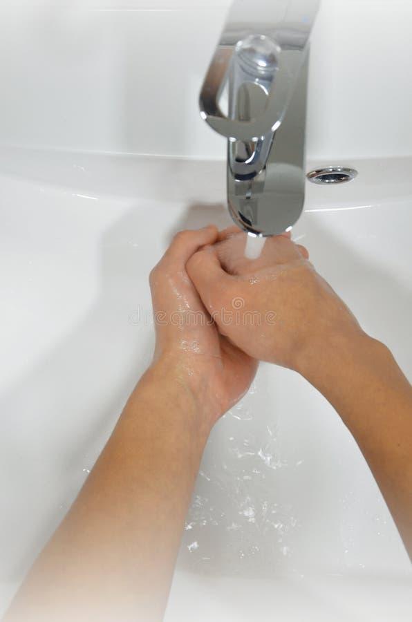 Mãos de lavagem com sabão sob o torneira com água imagem imagens de stock