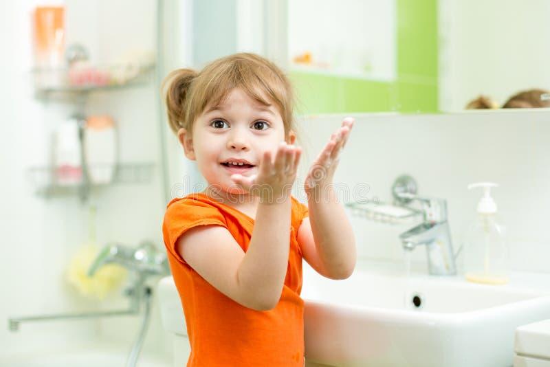 Mãos de lavagem da menina bonito no banheiro fotografia de stock royalty free