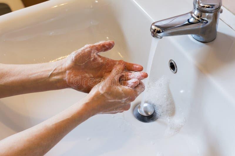 Mãos de lavagem da mulher com sabão imagens de stock