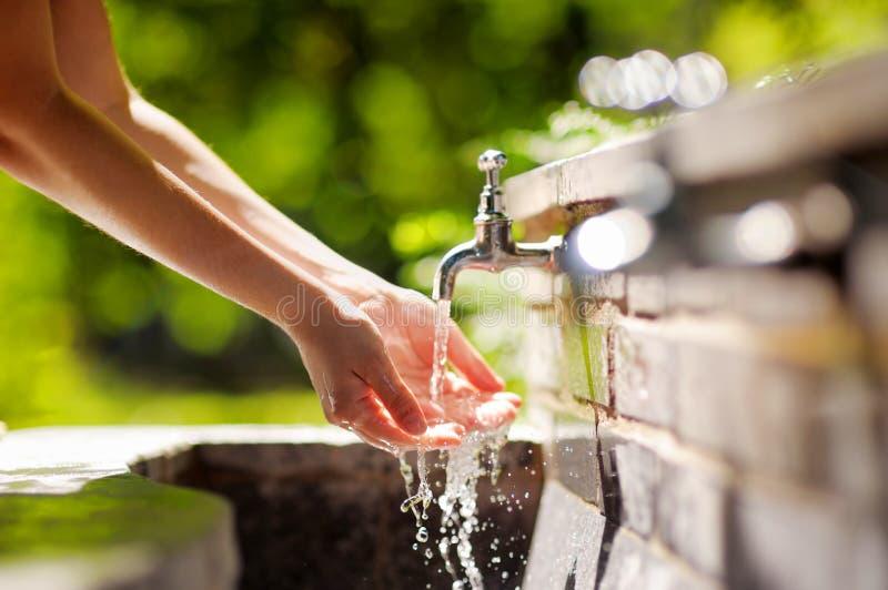 Mãos de lavagem da mulher em uma fonte da cidade imagem de stock