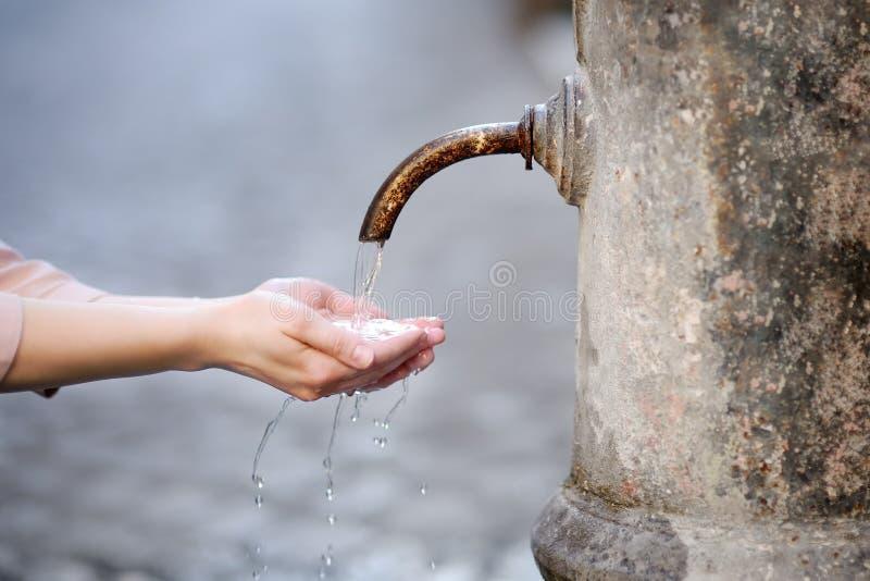 Mãos de lavagem da mulher em uma fonte da cidade em Roma, Itália imagens de stock royalty free