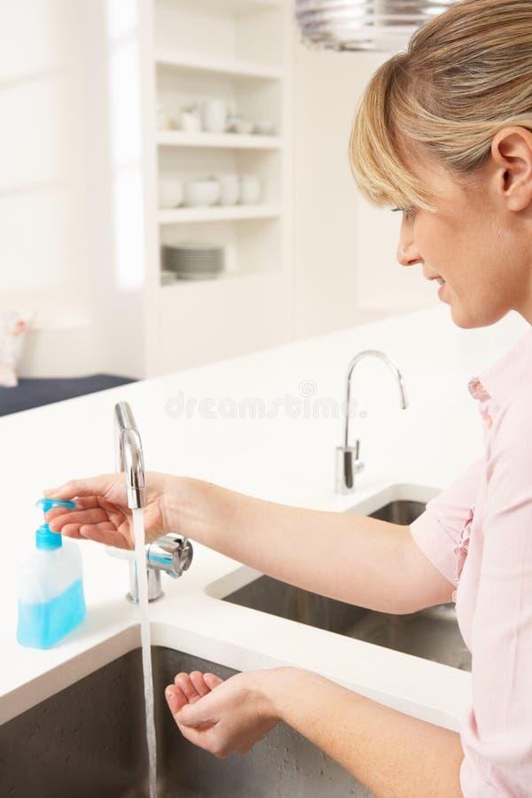Mãos de lavagem da mulher no dissipador de cozinha fotos de stock