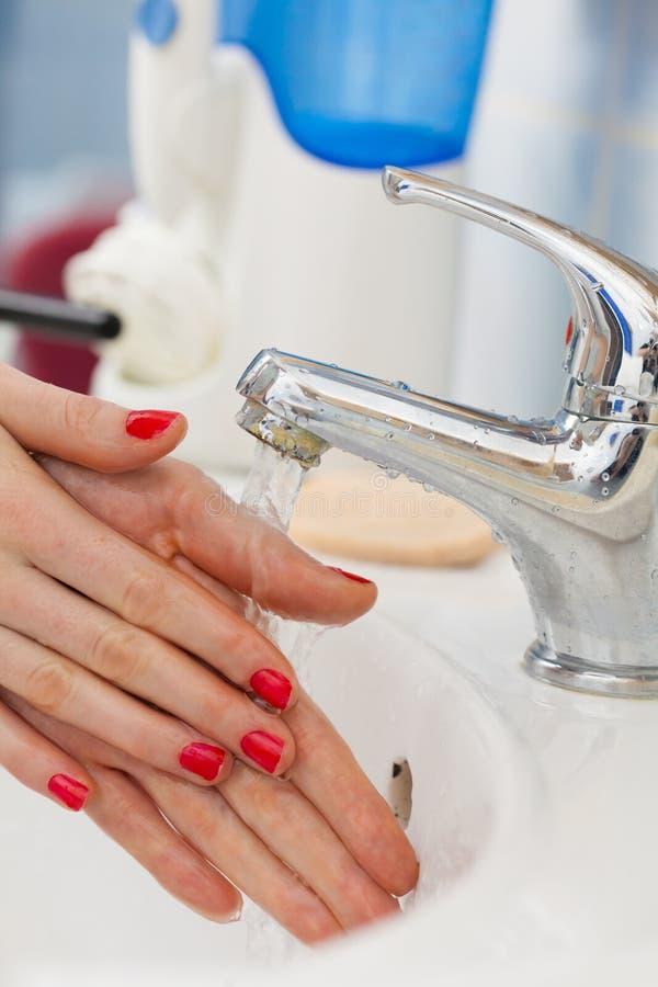 Mãos de lavagem da mulher sob o água da torneira de fluxo no banheiro foto de stock royalty free