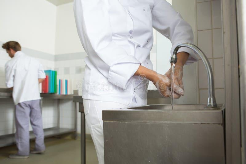 Mãos de lavagem do cozinheiro chefe antes do cozinheiro imagens de stock