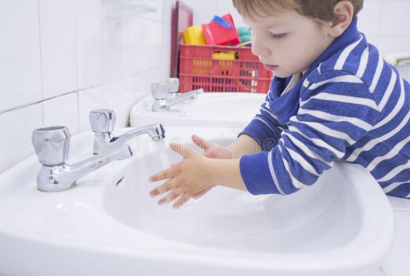 Mãos de lavagem do menino da criança no dissipador adaptado da escola fotografia de stock