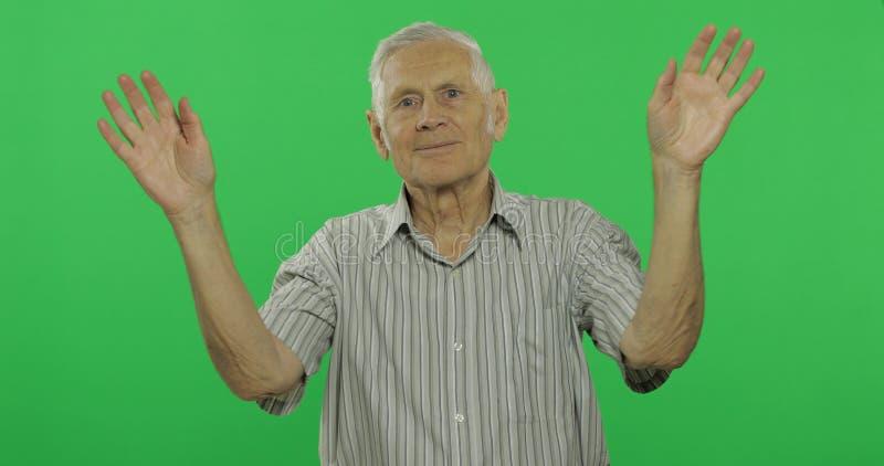 Mãos de ondulação do homem superior à câmera Ancião considerável no fundo chave do croma foto de stock royalty free