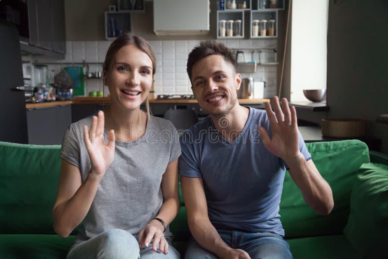 Mãos de ondulação de sorriso dos pares que sentam-se no sofá que olha a câmera imagens de stock