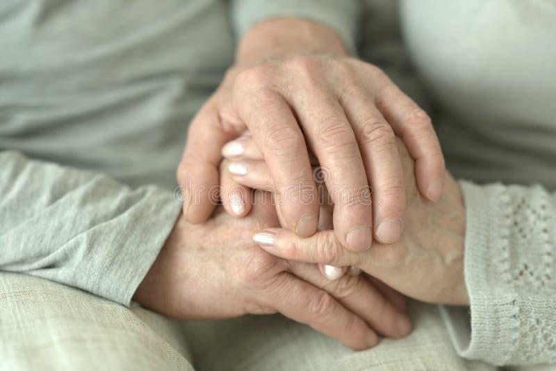 Mãos de pares idosos afetuosos imagem de stock royalty free