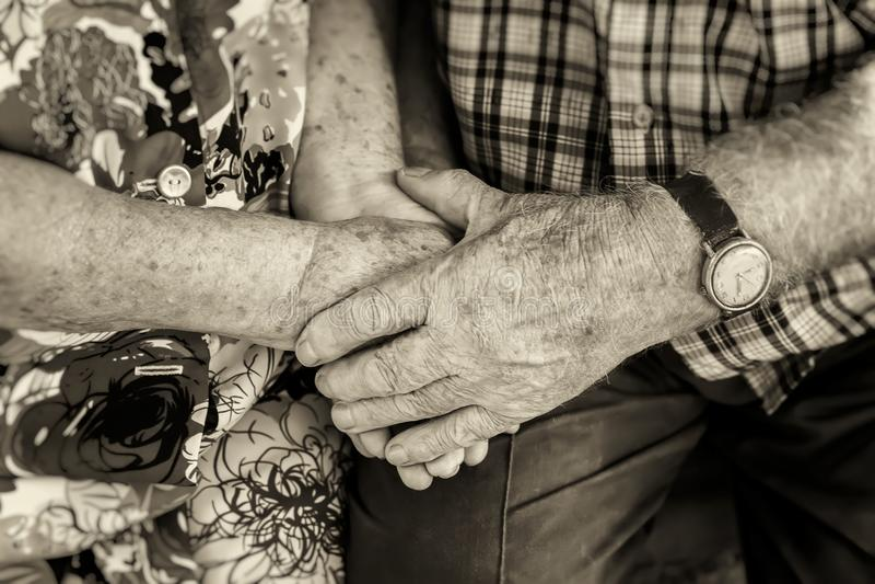 Mãos de pares idosos, mantendo as mãos dos sêniores unidos close-up, o conceito dos relacionamentos, a união e as pessoas adultas foto de stock royalty free
