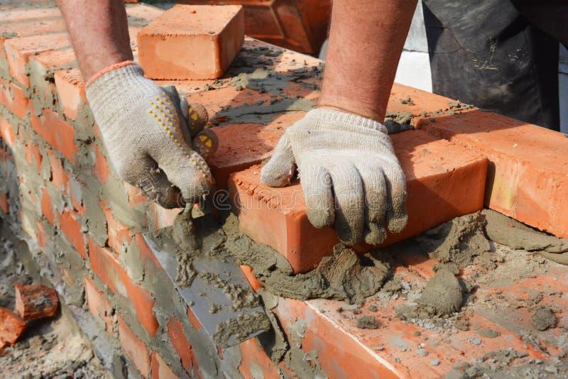 Mãos de pedreiro luvas de alvenaria tijolo novo muro de tijolos Masonry fechar imagem de stock