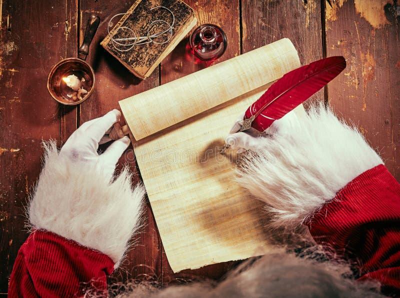 Mãos de Santa Claus que escrevem uma letra do Natal em um rolo do vintage com uma pena vermelha pela luz de vela em um de madeira imagens de stock