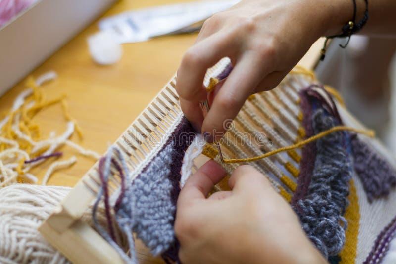 Mãos de tecelagem do tear vertical que trabalham lãs amarelas azuis imagem de stock royalty free