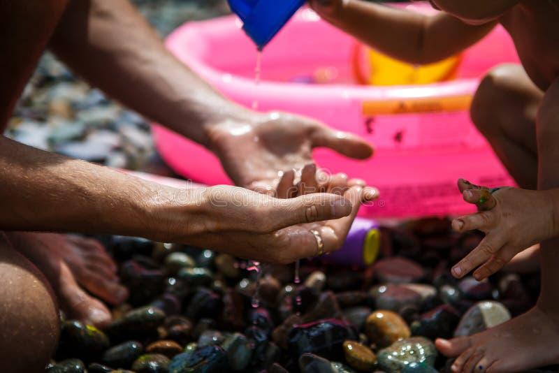 Mãos de um adulto e de uma criança que jogam em um Pebble Beach fotos de stock royalty free
