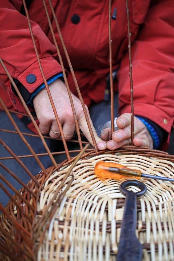 Mãos de um artesão que trabalha em uma cesta de vime foto de stock royalty free