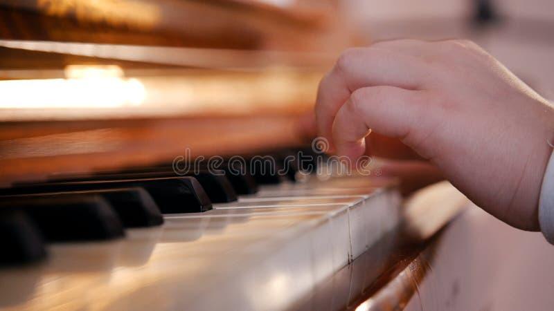 Mãos de um bebê que jogam o piano na lição de música na escola Fim acima fotografia de stock