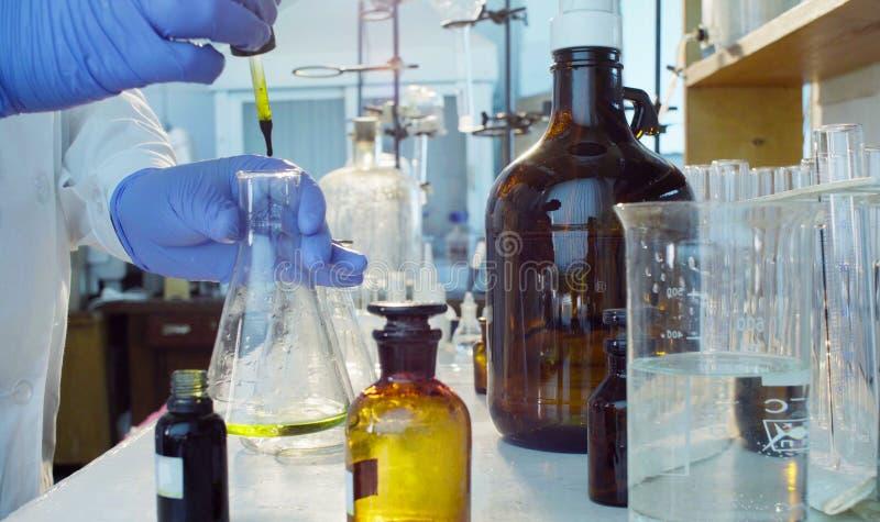 Mãos de um cientista que deixa cair um indicador às garrafas com uma solução imagens de stock royalty free