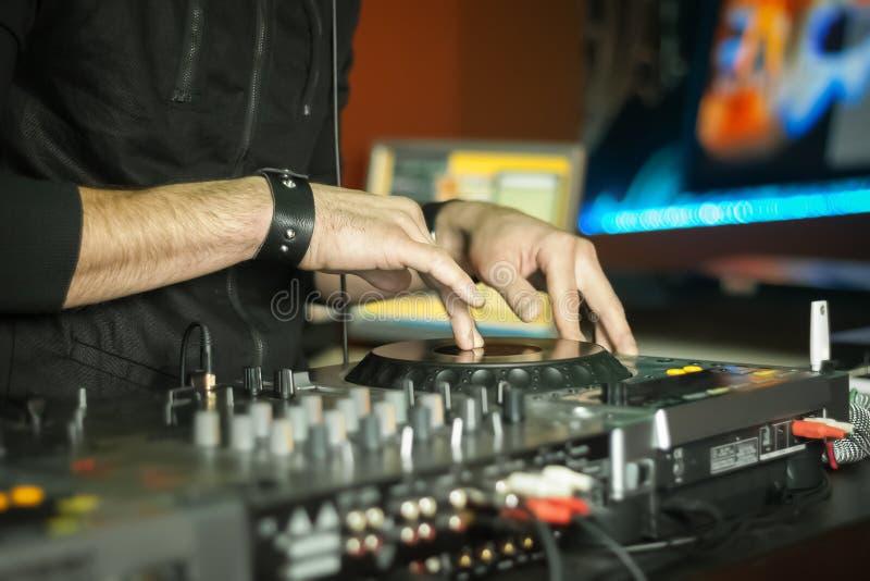 Mãos de um DJ que joga a música em um partido fotos de stock