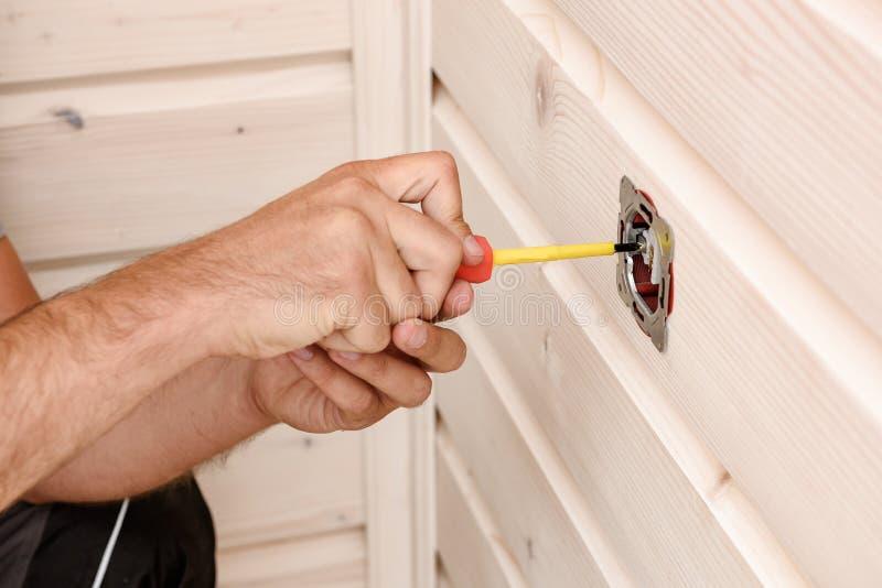 Mãos de um eletricista que instala um soquete, cortando um close up fotos de stock royalty free