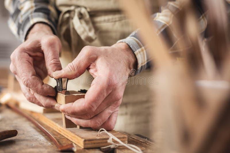 Mãos de um fabricante do instrumento que trabalha em uma curva de violino fotos de stock