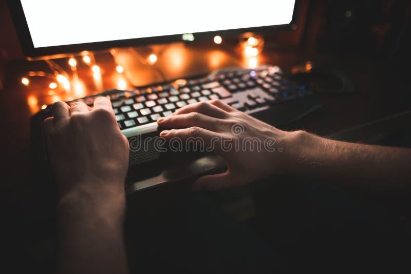 Mãos de um gamer novo que joga jogos de vídeo na noite no computador, mãos e fim do teclado acima foto de stock
