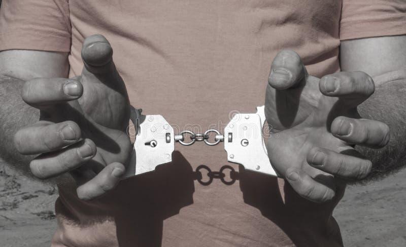 Mãos de um homem brutal nas algemas atrás de sua parte traseira em um t-shirt alaranjado Punição criminosa do aprisionamento na p foto de stock royalty free
