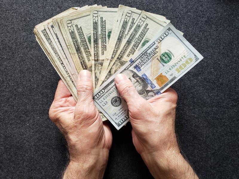 mãos de um homem mais idoso que guarda cédulas americanas dos dólares imagem de stock