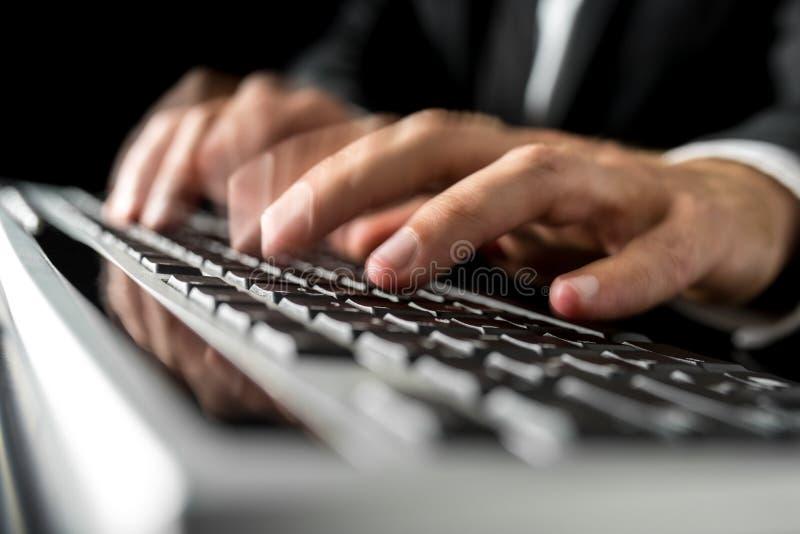 Mãos de um homem que datilografa rapidamente em um teclado de computador imagens de stock royalty free