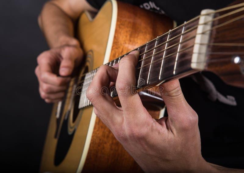 Mãos de um indivíduo novo que jogue a guitarra fotos de stock