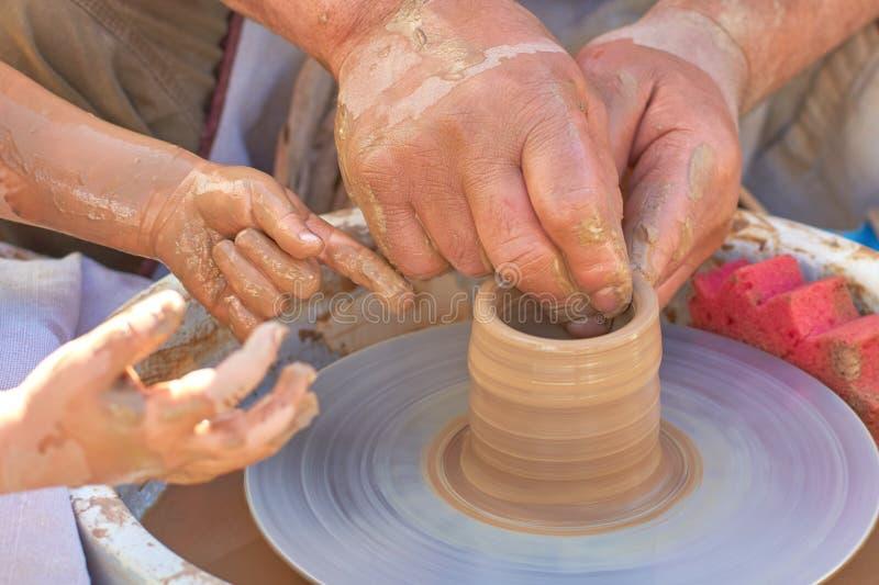 Mãos de um oleiro e de um estudante na argila, close-up fotografia de stock