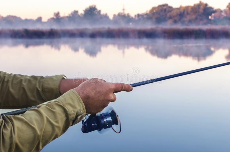 Mãos de um pescador com uma manhã do verão da haste e da bobina de gerencio no lago imagem de stock