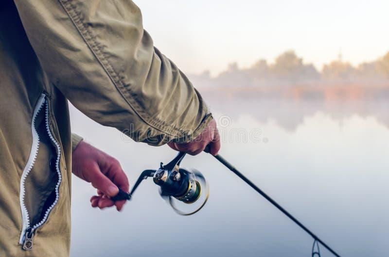 Mãos de um pescador com uma manhã do verão da haste e da bobina de gerencio no lago fotografia de stock