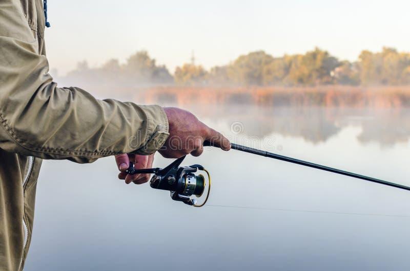 Mãos de um pescador com uma manhã do verão da haste e da bobina de gerencio no lago fotografia de stock royalty free