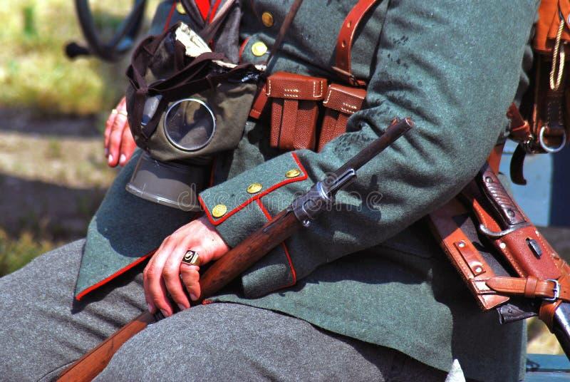 Mãos de um soldado-reenactor alemão que guarda uma arma imagem de stock