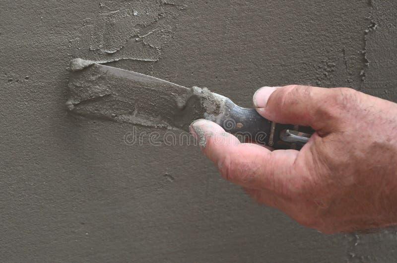 Mãos de um trabalhador manual idoso com parede que emplastra ferramentas que renova a casa Estucador que renova paredes e cantos  fotos de stock