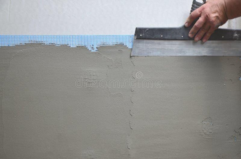 Mãos de um trabalhador manual idoso com parede que emplastra ferramentas que renova a casa Estucador que renova paredes e cantos  imagem de stock