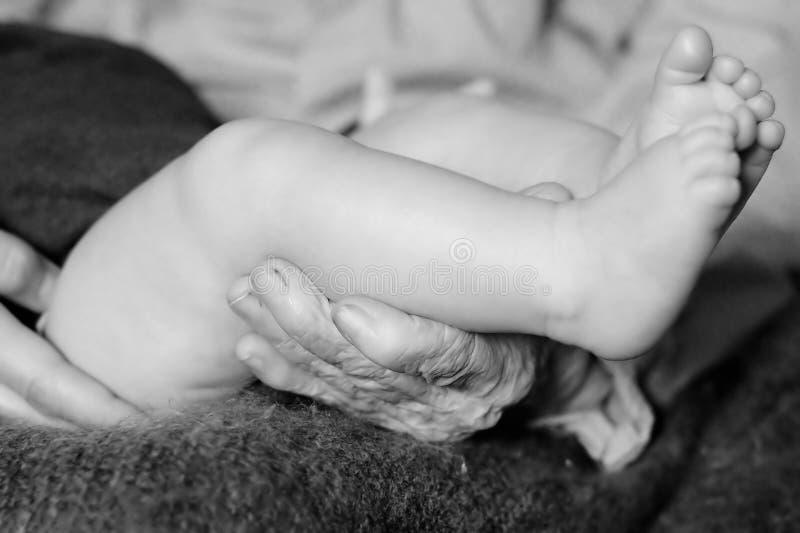 Mãos de uma avó que guarda o bebê pequeno imagem de stock