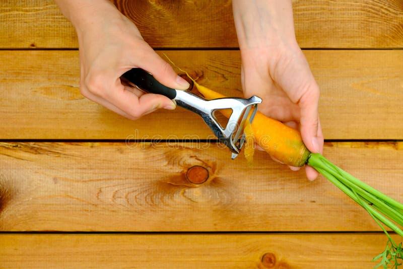 Mãos de uma cenoura da casca da jovem mulher com descascador fotos de stock royalty free