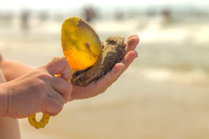 Mãos de uma criança fechada. Uma criança brinca com areia e uma pá na praia imagem de stock