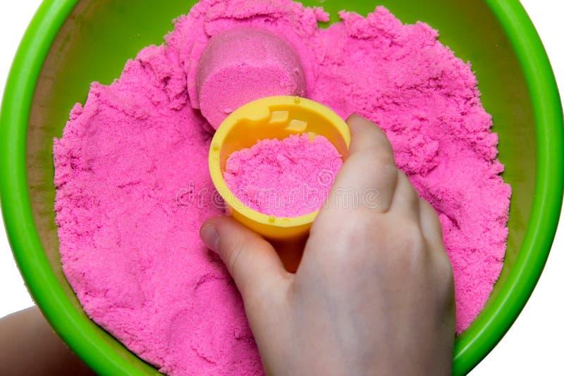 Mãos de uma criança que joga com a areia mágica cor-de-rosa fotos de stock