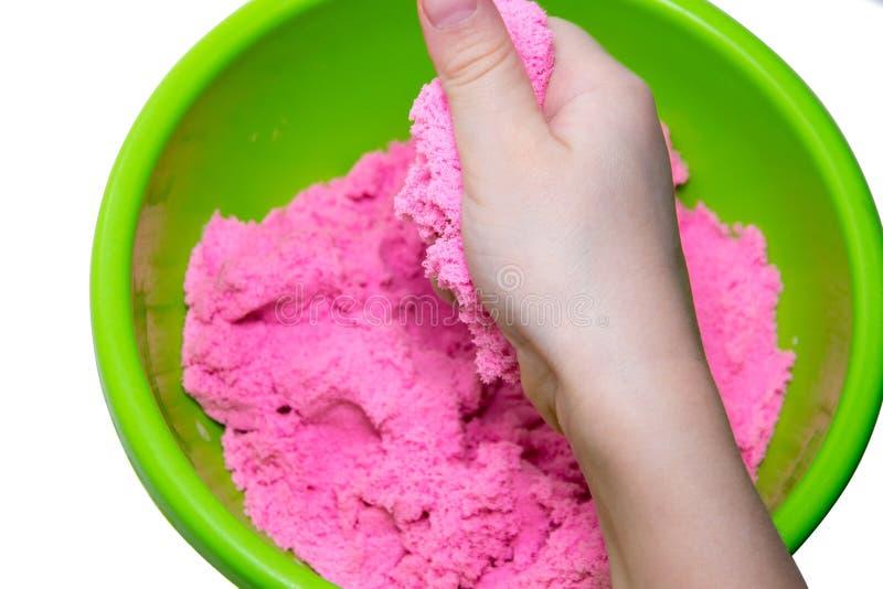 Mãos de uma criança que joga com a areia mágica cor-de-rosa imagens de stock