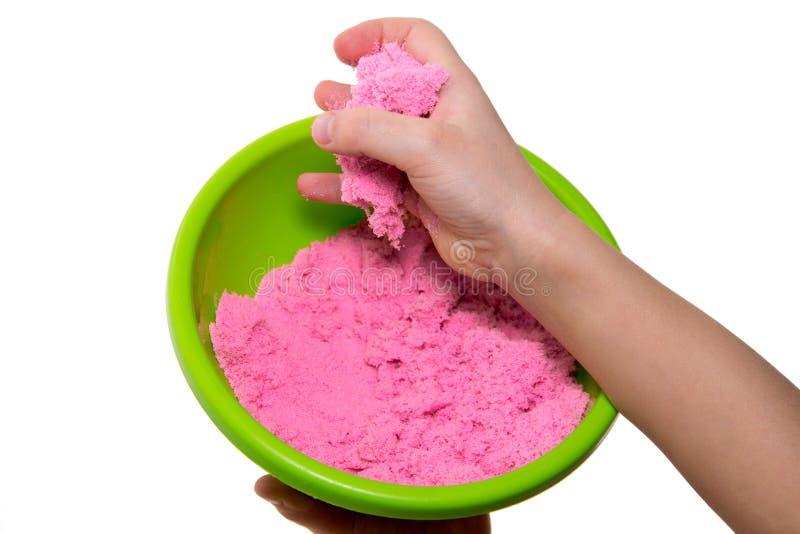 Mãos de uma criança que joga com a areia mágica cor-de-rosa fotografia de stock royalty free