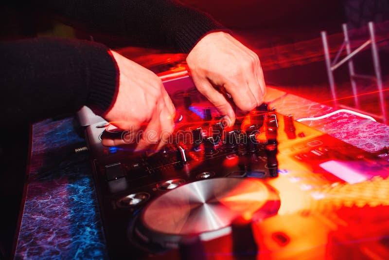 Mãos de uma música de jogo e de mistura profissional do DJ com efeitos da luz brilhantes foto de stock