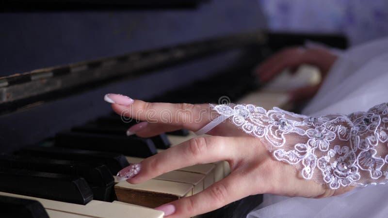 Mãos de uma menina que joga o piano Close-up os dedos fêmeas jogam um instrumento musical do teclado Indústria musical fotografia de stock